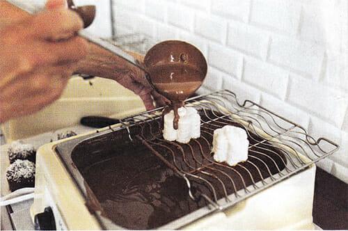 Übergießen der Schaumfülle mit Schokolade